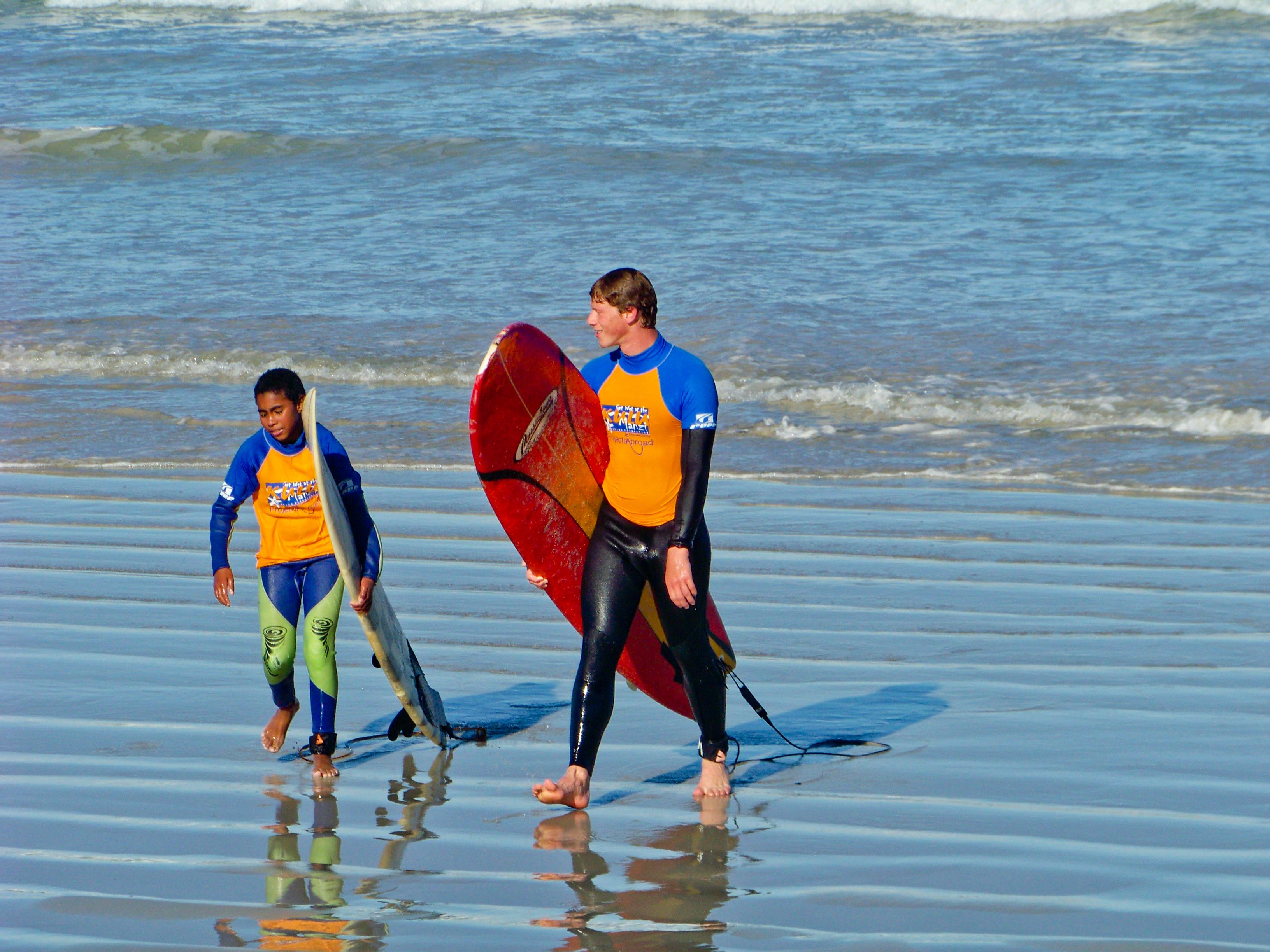 A young surfer and a volunteer walk along the beach during a project dedicated to teaching sport abroad.
